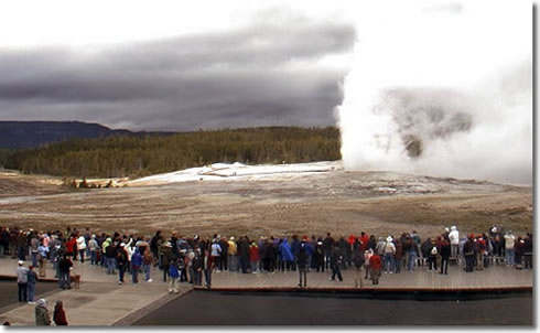Visitors watch Old Faithful start to erupt after the Yellowstone National Park Quarter ceremony ended.